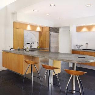Foto di una cucina minimalista di medie dimensioni con lavello sottopiano, ante lisce, ante in legno scuro, top in cemento, elettrodomestici in acciaio inossidabile, pavimento in cemento e pavimento nero