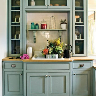 Beach style kitchen designs - Inspiration for a beach style kitchen remodel in Birmingham with a drop-in sink, beaded inset cabinets, blue cabinets, wood countertops, white backsplash and subway tile backsplash