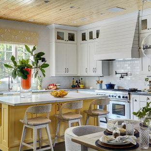 Bild på ett lantligt vit vitt kök, med en rustik diskho, luckor med infälld panel, gula skåp, vitt stänkskydd, stänkskydd i tunnelbanekakel, rostfria vitvaror, mellanmörkt trägolv, en köksö, brunt golv och bänkskiva i kvarts