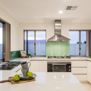 Inspiration for a contemporary u-shaped eat-in kitchen in Perth with a drop-in sink, flat-panel cabinets, white cabinets, blue splashback, glass sheet splashback, black appliances, a peninsula, beige floor and white benchtop.