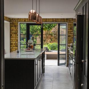 ロンドンのインダストリアルスタイルのおしゃれなキッチン (アンダーカウンターシンク、シェーカースタイル扉のキャビネット、黒いキャビネット、シルバーの調理設備、ベージュの床、グレーのキッチンカウンター) の写真
