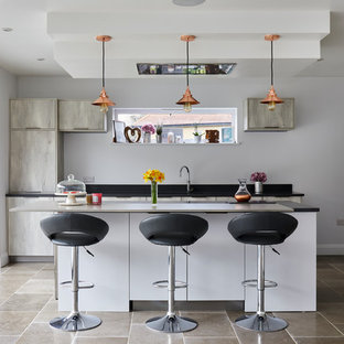 Photo of a contemporary l-shaped kitchen in London with a submerged sink, flat-panel cabinets, light wood cabinets, white splashback, black appliances, an island, grey floors and black worktops.