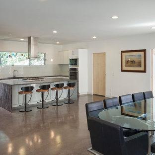 ダラスの広いモダンスタイルのおしゃれなキッチン (ドロップインシンク、フラットパネル扉のキャビネット、白いキャビネット、ラミネートカウンター、白いキッチンパネル、セラミックタイルのキッチンパネル、シルバーの調理設備、コンクリートの床、茶色い床、黒いキッチンカウンター) の写真
