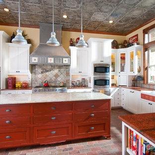 Idées déco pour une cuisine campagne en L avec un évier de ferme, un placard à porte shaker, des portes de placard rouges, une crédence multicolore, un électroménager en acier inoxydable, un îlot central et un sol multicolore.