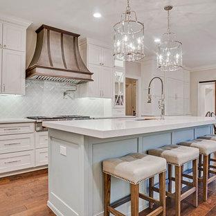 Exempel på ett stort klassiskt vit vitt kök, med luckor med profilerade fronter, vita skåp, bänkskiva i kvarts, blått stänkskydd, stänkskydd i keramik, integrerade vitvaror, mellanmörkt trägolv, en köksö och brunt golv