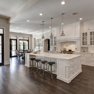 Example of a classic dark wood floor open concept kitchen design in Dallas with recessed-panel cabinets, white cabinets, white backsplash and stone slab backsplash