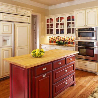 Kitchen - traditional kitchen idea in Dallas with glass-front cabinets, wood countertops and red cabinets