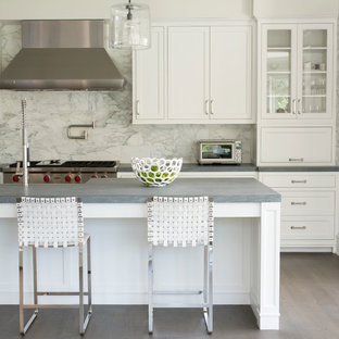 Mid-sized transitional eat-in kitchen inspiration - Eat-in kitchen - mid-sized transitional galley medium tone wood floor and gray floor eat-in kitchen idea in New York with recessed-panel cabinets, white cabinets, gray backsplash, stainless steel appliances, an island, marble backsplash, a farmhouse sink and quartz countertops