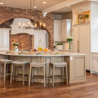 Küche in L-Form mit Quarzwerkstein-Arbeitsplatte, Rückwand aus Backstein, braunem Holzboden, Kücheninsel, Schrankfronten mit vertiefter Füllung, beigen Schränken, Elektrogeräten mit Frontblende, braunem Boden und beiger Arbeitsplatte in Denver