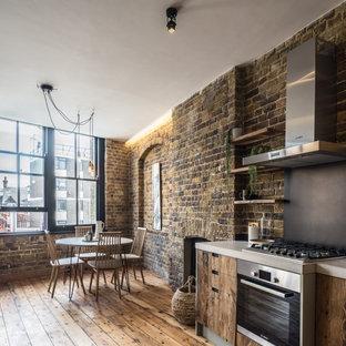 Foto på ett stort industriellt beige linjärt kök och matrum, med släta luckor, skåp i mellenmörkt trä, grått stänkskydd, rostfria vitvaror och mellanmörkt trägolv
