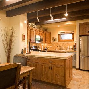 Idéer för att renovera ett litet amerikanskt kök, med en undermonterad diskho, släta luckor, skåp i ljust trä, kaklad bänkskiva, beige stänkskydd, stänkskydd i keramik, rostfria vitvaror och klinkergolv i keramik