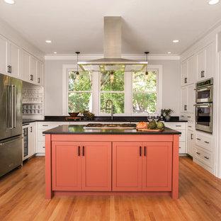 Idéer för mellanstora vintage svart u-kök, med skåp i shakerstil, orange skåp, rostfria vitvaror, mellanmörkt trägolv, en köksö, brunt golv, en undermonterad diskho och bänkskiva i koppar