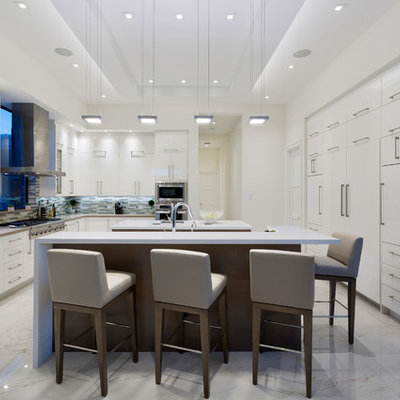 Large trendy u-shaped porcelain tile and white floor eat-in kitchen photo in Miami with flat-panel cabinets, white cabinets, quartz countertops, beige backsplash, glass tile backsplash, white appliances, two islands and white countertops