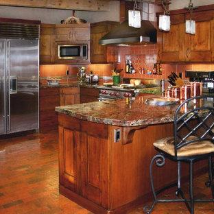 アルバカーキの中くらいのラスティックスタイルのおしゃれなキッチン (フラットパネル扉のキャビネット、中間色木目調キャビネット、御影石カウンター、赤いキッチンパネル、テラコッタタイルのキッチンパネル、シルバーの調理設備、レンガの床、赤い床) の写真
