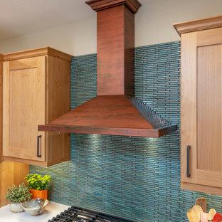 他の地域の広いサンタフェスタイルのおしゃれなアイランドキッチン (アンダーカウンターシンク、シェーカースタイル扉のキャビネット、中間色木目調キャビネット、クオーツストーンカウンター、青いキッチンパネル、セラミックタイルのキッチンパネル、シルバーの調理設備、テラコッタタイルの床、オレンジの床、白いキッチンカウンター) の写真