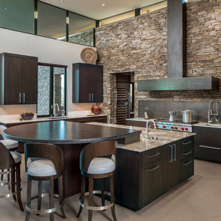 Photo of a large contemporary u-shaped kitchen in Phoenix with an undermount sink, flat-panel cabinets, dark wood cabinets, quartzite benchtops, black splashback, stainless steel appliances, porcelain floors, with island, beige floor and beige benchtop.