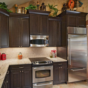 Small southwestern enclosed kitchen designs - Example of a small southwest single-wall porcelain floor enclosed kitchen design in Dallas with an undermount sink, raised-panel cabinets, dark wood cabinets, granite countertops, mosaic tile backsplash, stainless steel appliances and no island