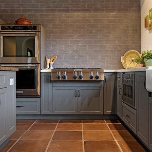 フェニックスの広いサンタフェスタイルのおしゃれなキッチン (エプロンフロントシンク、シェーカースタイル扉のキャビネット、グレーのキャビネット、木材カウンター、グレーのキッチンパネル、レンガのキッチンパネル、シルバーの調理設備、テラコッタタイルの床、茶色い床、茶色いキッチンカウンター) の写真