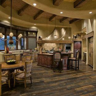 Modelo de cocina comedor de estilo americano con fregadero sobremueble, armarios con paneles con relieve, salpicadero beige y electrodomésticos con paneles