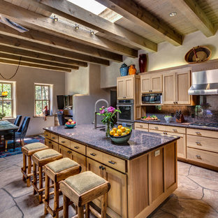 Mid-sized southwestern eat-in kitchen ideas - Example of a mid-sized southwest l-shaped beige floor eat-in kitchen design in Albuquerque with shaker cabinets, medium tone wood cabinets, stainless steel appliances, an island, an undermount sink, granite countertops, blue backsplash and stone tile backsplash