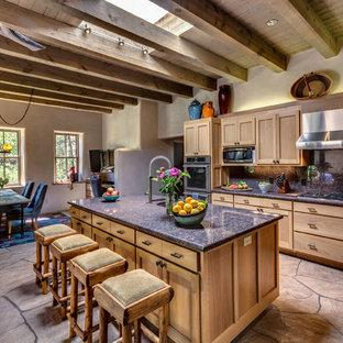 アルバカーキの中くらいのサンタフェスタイルのおしゃれなキッチン (シェーカースタイル扉のキャビネット、中間色木目調キャビネット、シルバーの調理設備、アンダーカウンターシンク、御影石カウンター、青いキッチンパネル、石タイルのキッチンパネル、ベージュの床) の写真