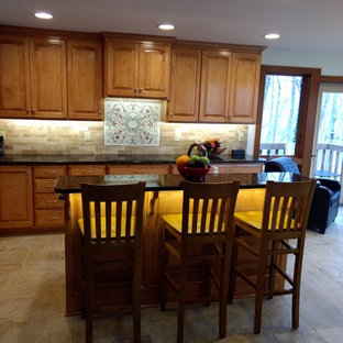 Southwestern eat-in kitchen designs - Southwest single-wall ceramic floor and beige floor eat-in kitchen photo in Columbus with medium tone wood cabinets, granite countertops, multicolored backsplash and an island