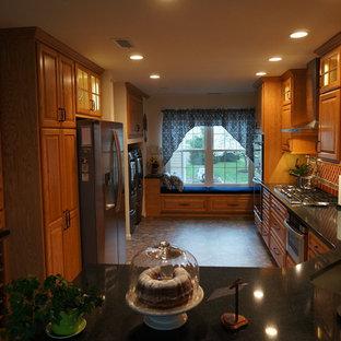 Cette image montre une petite cuisine américaine sud-ouest américain en L avec un évier encastré, un placard avec porte à panneau surélevé, des portes de placard en bois brun, un plan de travail en quartz modifié, une crédence marron, une crédence en carreau de terre cuite, un électroménager en acier inoxydable, un sol en linoléum et aucun îlot.