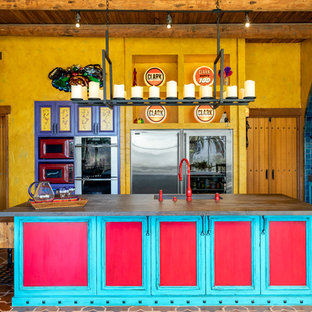 Southwestern kitchen inspiration - Inspiration for a southwestern terra-cotta floor and multicolored floor kitchen remodel in San Diego with an undermount sink, recessed-panel cabinets, turquoise cabinets, stainless steel appliances and an island
