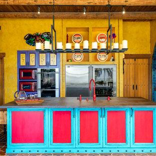サンディエゴのサンタフェスタイルのおしゃれなアイランドキッチン (アンダーカウンターシンク、落し込みパネル扉のキャビネット、ターコイズのキャビネット、シルバーの調理設備の、テラコッタタイルの床、マルチカラーの床) の写真