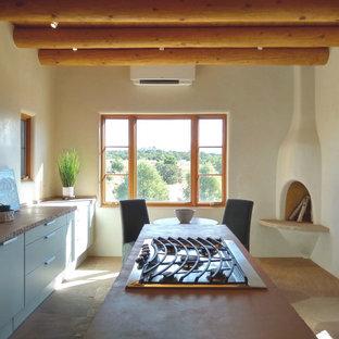 他の地域の中サイズのサンタフェスタイルのおしゃれなキッチン (アンダーカウンターシンク、フラットパネル扉のキャビネット、グレーのキャビネット、シルバーの調理設備の、ピンクの床) の写真