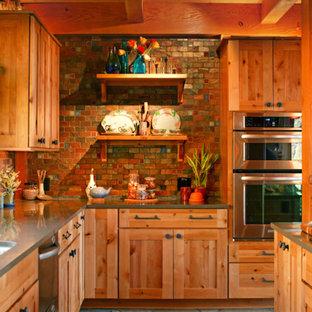 他の地域の広いサンタフェスタイルのおしゃれなキッチン (シェーカースタイル扉のキャビネット、中間色木目調キャビネット、クオーツストーンカウンター、マルチカラーのキッチンパネル、セラミックタイルのキッチンパネル、シルバーの調理設備、マルチカラーの床) の写真