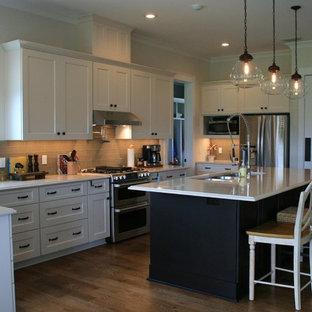 Immagine di una cucina classica di medie dimensioni con lavello a tripla vasca, ante con riquadro incassato, ante beige, top in quarzo composito, paraspruzzi grigio, paraspruzzi con piastrelle di vetro, elettrodomestici in acciaio inossidabile, pavimento in legno massello medio e isola