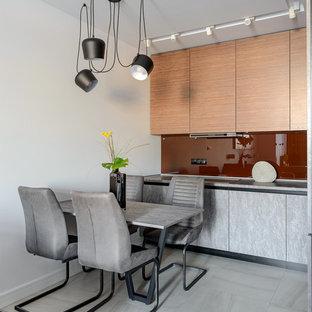 Свежая идея для дизайна: кухня-гостиная в современном стиле с плоскими фасадами, светлыми деревянными фасадами, красным фартуком, фартуком из стекла, серым полом и серой столешницей - отличное фото интерьера