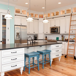Traditional kitchen ideas - Inspiration for a timeless l-shaped light wood floor kitchen remodel in Wilmington with white backsplash, subway tile backsplash and white cabinets