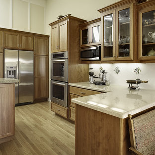 Example of a classic u-shaped kitchen design in San Francisco with shaker cabinets, medium tone wood cabinets, white backsplash and stainless steel appliances