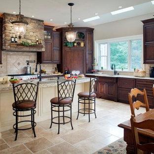 Klassische Wohnküche mit Elektrogeräten mit Frontblende, Granit-Arbeitsplatte, profilierten Schrankfronten, dunklen Holzschränken, Küchenrückwand in Beige und Kalk-Rückwand in Philadelphia