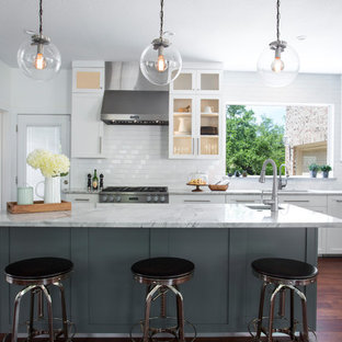 Transitional kitchen appliance - Inspiration for a transitional l-shaped dark wood floor and brown floor kitchen remodel in Austin with an undermount sink, shaker cabinets, gray cabinets, white backsplash, subway tile backsplash, stainless steel appliances, an island and gray countertops