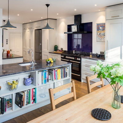Transitional medium tone wood floor and brown floor eat-in kitchen photo in London with an undermount sink, shaker cabinets, gray cabinets, glass sheet backsplash, black appliances, an island and gray countertops
