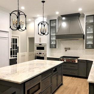 ローリーの大きいカントリー風おしゃれなキッチン (エプロンフロントシンク、シェーカースタイル扉のキャビネット、グレーのキャビネット、御影石カウンター、白いキッチンパネル、サブウェイタイルのキッチンパネル、パネルと同色の調理設備、淡色無垢フローリング、茶色い床、ベージュのキッチンカウンター) の写真