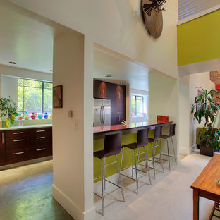 Large modern galley kitchen/diner in Seattle with a double-bowl sink, flat-panel cabinets, dark wood cabinets, glass worktops, green splashback, glass tiled splashback, stainless steel appliances, concrete flooring and an island.