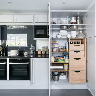 Photo of a traditional kitchen in London with shaker cabinets, grey cabinets, grey splashback, glass sheet splashback, black appliances and grey floors.