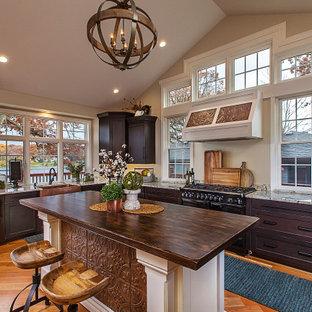デトロイトの大きいエクレクティックスタイルのおしゃれなキッチン (エプロンフロントシンク、落し込みパネル扉のキャビネット、ヴィンテージ仕上げキャビネット、木材カウンター、パネルと同色の調理設備、無垢フローリング、茶色い床) の写真