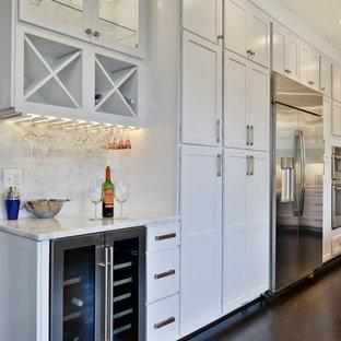 Modelo de cocina comedor moderna, grande, con fregadero sobremueble, puertas de armario blancas, encimera de cuarcita, salpicadero blanco, salpicadero de travertino, electrodomésticos de acero inoxidable, suelo de madera oscura, una isla, suelo marrón y encimeras blancas