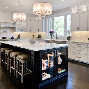 ワシントンD.C.の広いモダンスタイルのおしゃれなキッチン (エプロンフロントシンク、白いキャビネット、珪岩カウンター、白いキッチンパネル、トラバーチンのキッチンパネル、シルバーの調理設備、濃色無垢フローリング、茶色い床、白いキッチンカウンター) の写真