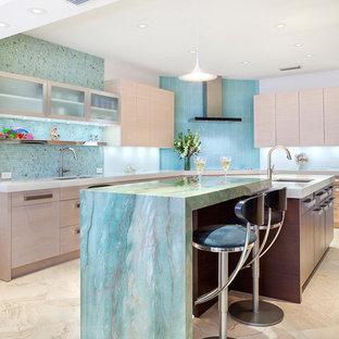 Bild på ett stort funkis grön grönt kök, med en undermonterad diskho, släta luckor, skåp i ljust trä, granitbänkskiva, grönt stänkskydd, glaspanel som stänkskydd, integrerade vitvaror, marmorgolv, flera köksöar och brunt golv