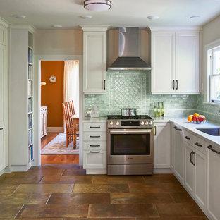 サンフランシスコの中サイズの地中海スタイルのおしゃれなキッチン (アンダーカウンターシンク、落し込みパネル扉のキャビネット、白いキャビネット、クオーツストーンカウンター、青いキッチンパネル、セラミックタイルのキッチンパネル、シルバーの調理設備の、磁器タイルの床、アイランドなし、茶色い床、ベージュのキッチンカウンター) の写真