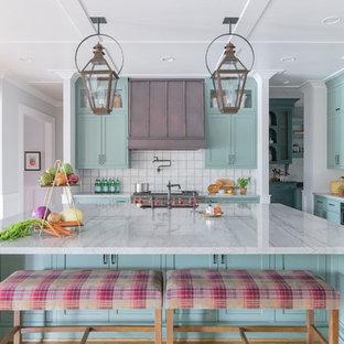 Idée de décoration pour une grand cuisine tradition en L avec un évier de ferme, un placard à porte shaker, des portes de placard bleues, une crédence blanche, un électroménager en acier inoxydable, un sol en bois brun, un îlot central, un sol marron et un plan de travail blanc.