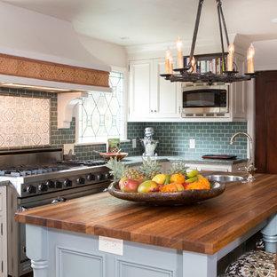 ロサンゼルスの中サイズの地中海スタイルのおしゃれなアイランドキッチン (ドロップインシンク、インセット扉のキャビネット、白いキャビネット、御影石カウンター、青いキッチンパネル、セラミックタイルのキッチンパネル、シルバーの調理設備の、テラコッタタイルの床) の写真