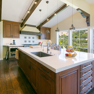 Southwestern eat-in kitchen designs - Southwest dark wood floor and brown floor eat-in kitchen photo in San Francisco with dark wood cabinets, quartz countertops, ceramic backsplash, colored appliances and an island