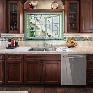 ロサンゼルスの中サイズの地中海スタイルのおしゃれなキッチン (ダブルシンク、落し込みパネル扉のキャビネット、濃色木目調キャビネット、タイルカウンター、緑のキッチンパネル、セラミックタイルのキッチンパネル、シルバーの調理設備の、セラミックタイルの床) の写真